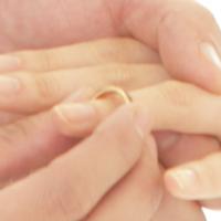 左手の薬指に指輪をはめようとしている人